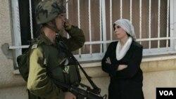 Seorang wanita Palestina berdiri di dekat tentara Israel saat aksi protes di Tepi Barat (dokumentasi).
