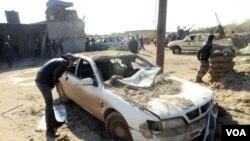 ຜູ້ຊາຍຄົນນຶ່ງກຳລັງກວດເບິ່ງລົດ ທີຖືກວາງລະເບີດ ຢູ່ໄກ້ຄ້າຍ ທະຫານ ທີ່ເມືອງ Benghazi ປະເທດ Libya
