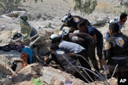 This photo provided by the Syrian Civil Defense White Helmets, which has been authenticated based on its contents and other AP reporting, shows Civil Defense workers searching through the rubble after airstrikes hit in Khan Sheikhoun.