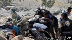 This photo provided by the Syrian Civil Defense White Helmets, which has been authenticated based on its contents and other AP reporting, shows Civil Defense workers searching through the rubble after airstrikes hit in Khan Sheikhoun, in the northern prov