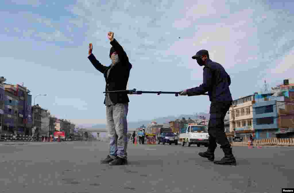 A police officer maintains distance as he detains a man defying the lockdown imposed by the government amid concerns about the spread of coronavirus disease (COVID-19), in Kathmandu, Nepal.