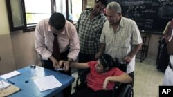 An Egyptian election worker helps a disabled woman in a wheelchair to vote at a polling station during the second day of the presidential runoff in Cairo, June 17, 2012.