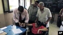 6月17日在开罗的一个投票战,一位选举工作人员帮助一位残疾人投票