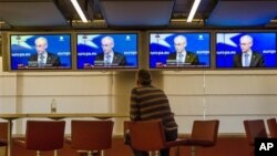 A man follows the media conference of European Council President Van Rompuy at the European Council building, Brussels, Feb. 8, 2013.