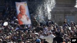 """Le pape François passe devant une bannière représentant saint Jean-Paul II mentionnant en italien """"meilleurs vœux"""", lors d'une audience publique sur la place Saint-Pierre au Vatican, le 22 octobre 2016."""
