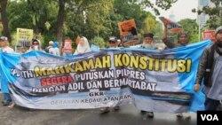 Para peserta aksi di sekitar gedung Mahkamah Konstitusi di Jakarta hari Jumat (14/6). (VOA/Sasmito)