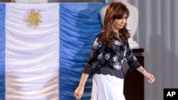 FILE - Argentina's President Cristina Fernandez walks past an Argentine flag at the Casa Rosada government palace in Buenos Aires, Argentina.