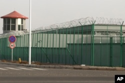 In this Dec. 3, 2018, photo, a guard tower and barbed wire fences are seen around a facility in the Kunshan Industrial Park in Artux in western China's Xinjiang region. This is one of a growing number of internment camps in the Xinjiang region.