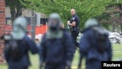 Un policía observa el trabajo de oficiales federales en busca de pruebas en el caso de las cartas envenenadas enviadas al presidente Obama y otros funcionarios.
