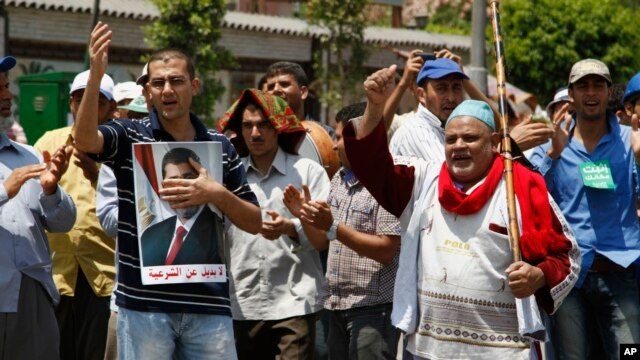 Supporters of Egypt's ousted President Mohammed Morsi chant slogans at a sit-in in Nasser City, suburb of Cairo, July 7, 2013.