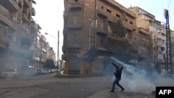 Một người biểu tình ở thành phố Homs quăng trả lại một quả bom xăng vào lực lượng an ninh. trong khi cảnh sát Syria dùng hơi cay để giải tán khoảng 70.000 người xuống đường biểu tình