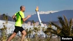 2月12日在索契,一名穿短袖短裤的男子在跑步,背景是奥林匹克公园