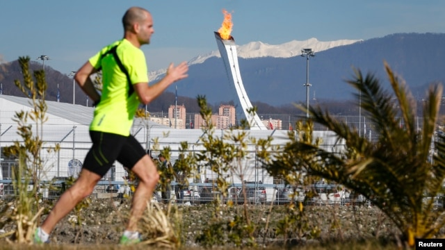 A man jogs on a sunny day as the Olympic Cauldron and flame are seen in the background in the Olympic Park during the 2014 Winter Olympic Games, Feb. 12, 2014.