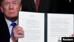 Tổng thống Donald Trump giơ bản thông tri loan báo kế hoạch đánh thuế lên tài sản trí tuệ và các sản phẩm công nghệ cao của Trung Quốc, tại Nhà Trắng ở Washington, ngày 22 tháng 3, 2018.