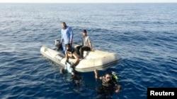 Anggota penjaga pantai Libya menemukan tubuh migran yang tenggelam di perairan Tripoli, 23 Agustus 2014.