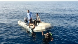 ATTENTION EDITORS - VISUAL COVERAGE OF SCENES OF INJURY OR DEATHMembers of Libya's coast guard recover the body of a migrant who drowned off Tripoli's coast, August 23, 2014. A wooden boat carrying up to 200 migrants has sunk just one kilometre (half a mi
