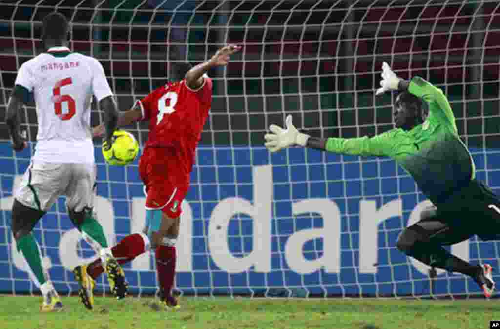 Iyanga of Equatorial Guinea scores goal while being challenged by goalkeeper Coundoul of Senegal during their African Nations Cup Group A soccer match at Estadio de Bata
