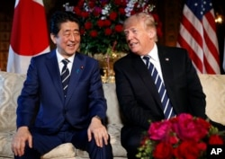 President Donald Trump and Japanese Prime Minister Shinzo Abe smile during their meeting at Trump's private Mar-a-Lago resort, April 17, 2018, in Palm Beach, Florida.