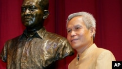 In this Aug. 31, 2005 file photo, Sombath Somphone of Laos, the winner of Ramon Magsaysay Award for Community Leadership in 2005, poses with the bust of the late Philippine president prior to receiving his award in ceremony at the Cultural Center of the Philippines in Manila.