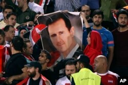 FILE - Syrian soccer fans hold a poster of their president, Bashar al-Assad, before a match with Iran, at Azadi Stadium, in Tehran, Iran, Sept. 5, 2017.