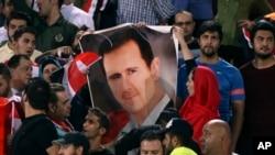 Des supporters de football syriens tiennent une affiche de leur président, Bachar al-Assad, avant un match contre l'Iran, au stade Azadi à Téhéran, en Iran, le 5 septembre 2017.