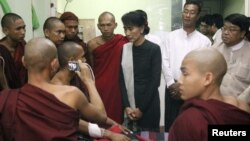 Burmese pro-democracy leader Aung San Suu Kyi visits Buddhist monks, wounded in a recent police crackdown on protesters against a copper mine project, November 29, 2012.