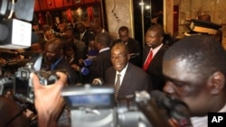 FILE: Zimbabwean President Robert Mugabe (C) briefs journalists on the progress made on the implementation of The Global Political Agreement , in Harare, Zimbabwe, August 15, 2012.