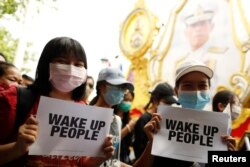 Pro-democracy protesters holding signs walk past a picture of Thai King Maha Vajiralongkorn during a rally near the Democracy Monument in Bangkok, Thailand, August 16, 2020.