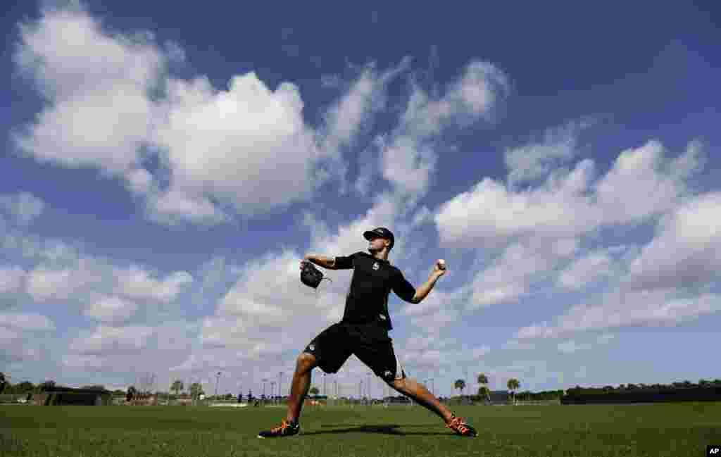 El jugador de fútbol de los Marlins de Miami, Dan Jennings lanza una bola antes de la inauguración oficial del inicio de la temporada de entrenamiento de primavera, en Jupiter, Florida.