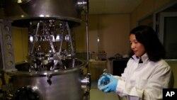 Представниця Комітету маси та пов'язаних кількостей тримає в руках міжнародний прототип кілограма
