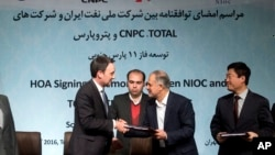 Head of the Middle East and North Africa division at Total, Stephane Michel, left, and managing director of the National Iranian Oil Company Ali Kardor, right, shake hands after signing documents in Tehran, Nov. 8, 2016.