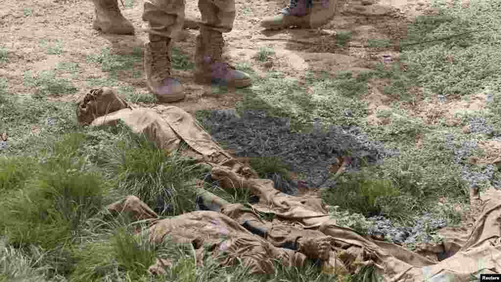 Des soldats nigériens regardent les cadavres en décomposition dans une fosse commune à Damasak, ville récemment reprise de Bokok Haram, au Nigeria, le 20 Mars 2015.