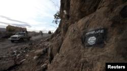 什叶派胡赛叛军驾驶着巡逻卡车,穿过画有伊斯兰旗帜的山坡(资料照片)