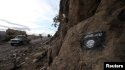 FILE - Shi'ite Houthi rebels drive a patrol truck past a Ansar al-Sharia flag painted on the side of a hill, along a road in Almnash, the main stronghold of Ansar al-Sharia, the local wing of al-Qaeda in the Arabian Peninsula (AQAP), in Rada, Nov. 22, 2014.