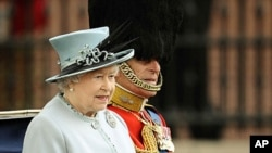 Britain's Queen Elizabeth and Prince Philip sit in a horse drawn carriage as they make their way from Buckingham Palace to attend the Trooping the Colour ceremony in central London, June 11, 2011