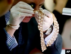 FILE - Christie's auction house appraiser David Warren examines a set of jewelry from Roumeliotes Collection, one of three sets of the Marcos Jewelry Collection, during appraisal at the Central Bank of the Philippines, Nov. 24, 2015 in Manila, Philippines.