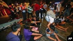 Orang-orang yang terluka dibantu oleh petugas keselamatan darurat di luar stasiun kereta setelah meledaknya sebuah bom pipa.