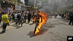 A Tibetan exile man, identified as Jampa Yeshi, runs engulfed in flames after self-immolating during a demonstration in New Delhi, India, Monday, March 26, 2012. Yeshi lit himself on fire and ran shouting through a protest in the Indian capital Monday, ju