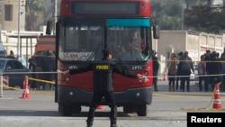 Petugas keamanan Mesir mengamankan lokasi ledakan bom pinggir jalan yang merusak sebuah bis di Kairo, Kamis (26/12).