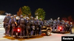 Police follow protesters during a march following Monday's grand jury decision in the shooting of Michael Brown in Ferguson, Missouri, in Los Angeles, California, Nov. 25, 2014.