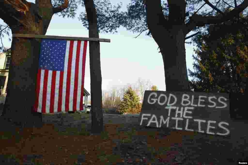 Cờ Mỹ và bảng gỗ với những hàng chữ cầu nguyện cho gia đình các nạn nhân gần trường tiểu học Sandy Hook ở Newtown, Connecticut, ngày 15/12/2012.