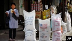 (File) A Palestinian girl walks past sacks of flour food aid from the United Nations and USAID at the Shatie refugee camp in Gaza City.