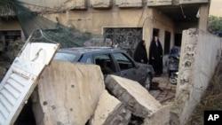 폭발로 파괴된 집을 살펴보는 이라크 여인