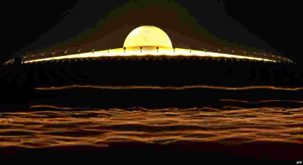 A long-exposure photo shows light streaking from the candles of Buddhist monks as they walk around a Pagoda on Makha Bhucha Day at the Dhammakaya Temple in Thailand. Makha Bhucha day is observed on the full moon of the third lunar month and commemorates the day when 1,250 monks gathered to be ordained by the Buddha.