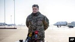 Presiden Ukraina Petro Poroshenko berbicara dengan media di bandar udara Borispol di luar Kyiv (18/2). (AP/Mikhail Palinchak)