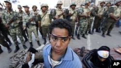An Egyptian protester boy stands in front of army soldiers who try to lead the protesters away from Tahrir Square in Cairo, Egypt Sunday morning, Feb. 13, 2011. Egypt's military took down the makeshift tents of protesters who camped out on the square in a