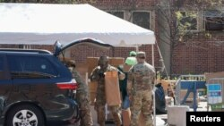 疫情期間,美國陸軍國民警衛隊員在紐約市曼哈頓哈萊姆區向民眾分發由多家市政府機構提供的免費食物。(2020年4月15日)
