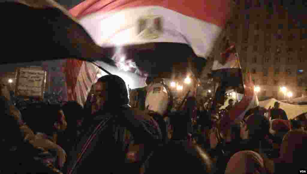 Penabuh drum dikelilingi bendera-bendera dalam jam-jam menegangkan sebelum pidato Presiden Mubarak di Kairo, 10 Februari 2011.