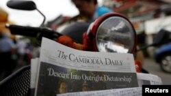 រូបឯកសារ៖ ស្ត្រីម្នាក់ទិញកាសែត The Cambodia Daily ដែលបោះពុម្ពផ្សាយលេខចុងក្រោយ នៅតូបលក់កាសែតមួយក្នុងរាជធានីភ្នំពេញ ប្រទេសកម្ពុជា ថ្ងៃទី៤ ខែកញ្ញា ឆ្នាំ២០១៧។ (Reuters / Samrang Pring)