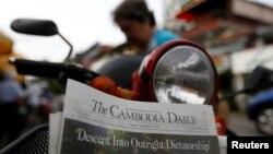 ស្ត្រីម្នាក់ទិញកាសែត The Cambodia Daily ដែលបោះពុម្ពផ្សាយលេខចុងក្រោយ នៅតូបលក់កាសែតមួយក្នុងរាជធានីភ្នំពេញ ប្រទេសកម្ពុជា ថ្ងៃទី៤ ខែកញ្ញា ឆ្នាំ២០១៧។ (Reuters / Samrang Pring)
